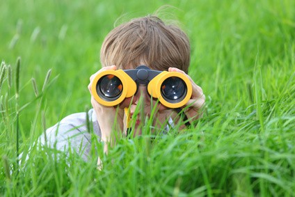 Boy hiding in grass using binoculars to spy on something