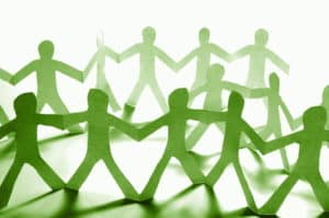paper cutout people all linked by their hands into a network