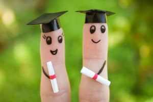 two fingers made up with pen faces and fake hats to look like students graduating