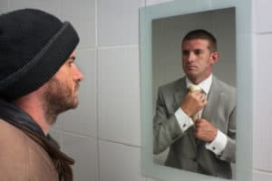Man in casual clothes looking at his reflection in the mirror - the reflection shows him in business wear