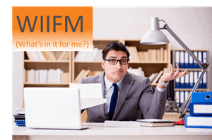 man at desk opening mail, with text 'WIIFM' overlaid
